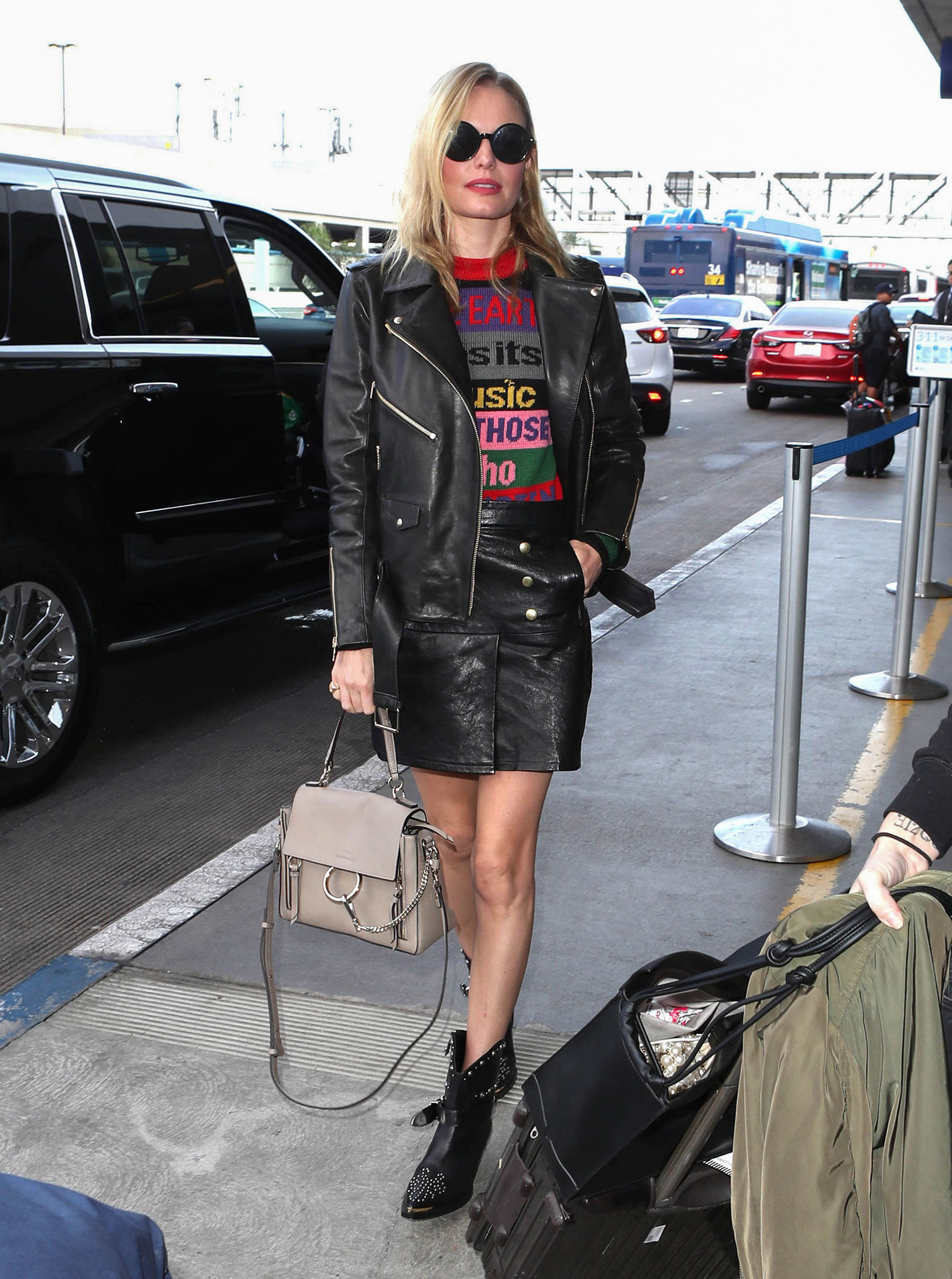 Kate Bosworth wears Etro's colorblock graphic sweater with an Anine Bing biker jacket, Frame leather mini skirt and moto boots.