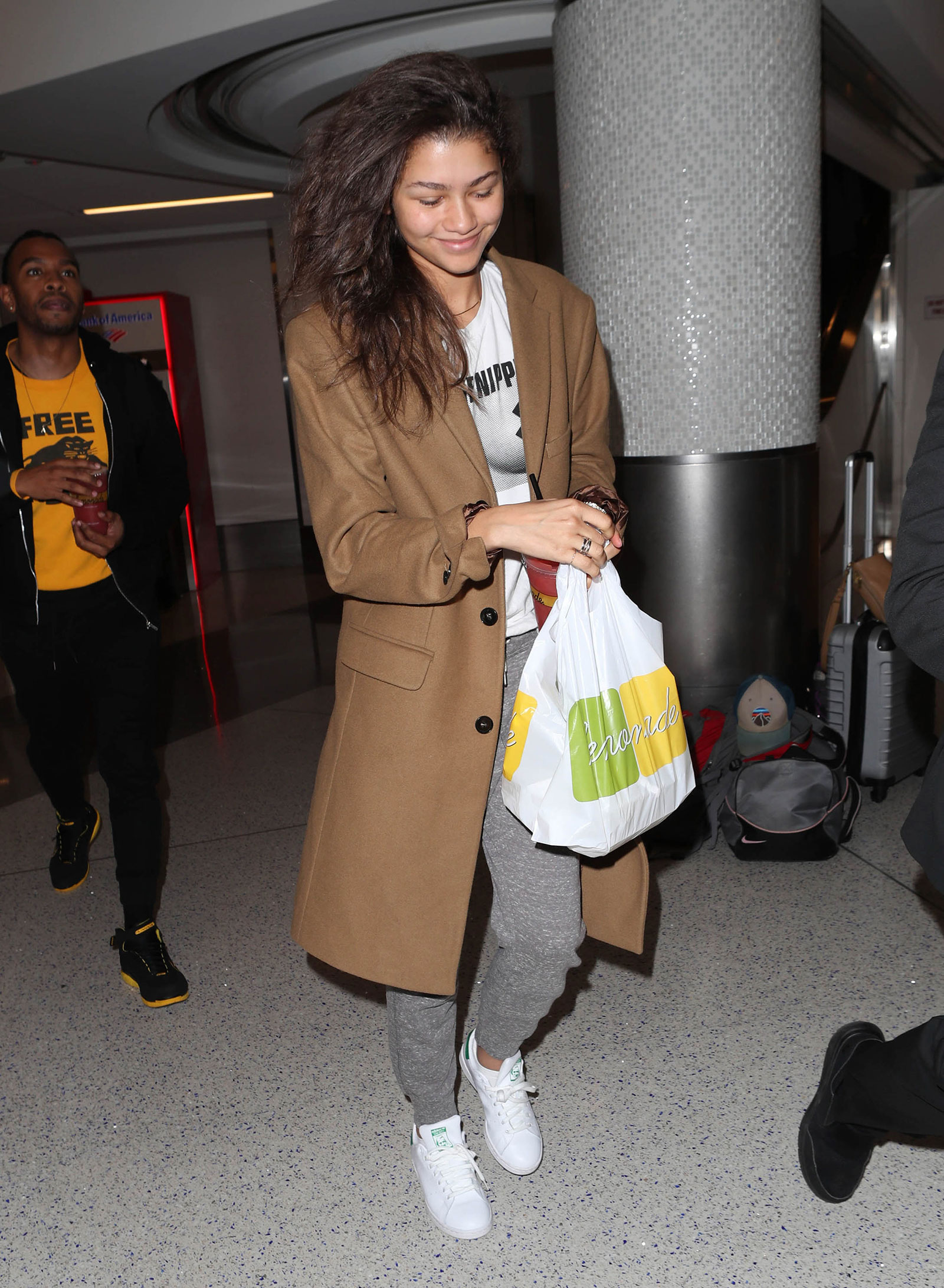 Zendaya wears a camel coat with a Free the Nipple t-shirt, gray joggers and Stan Smith sneakers.