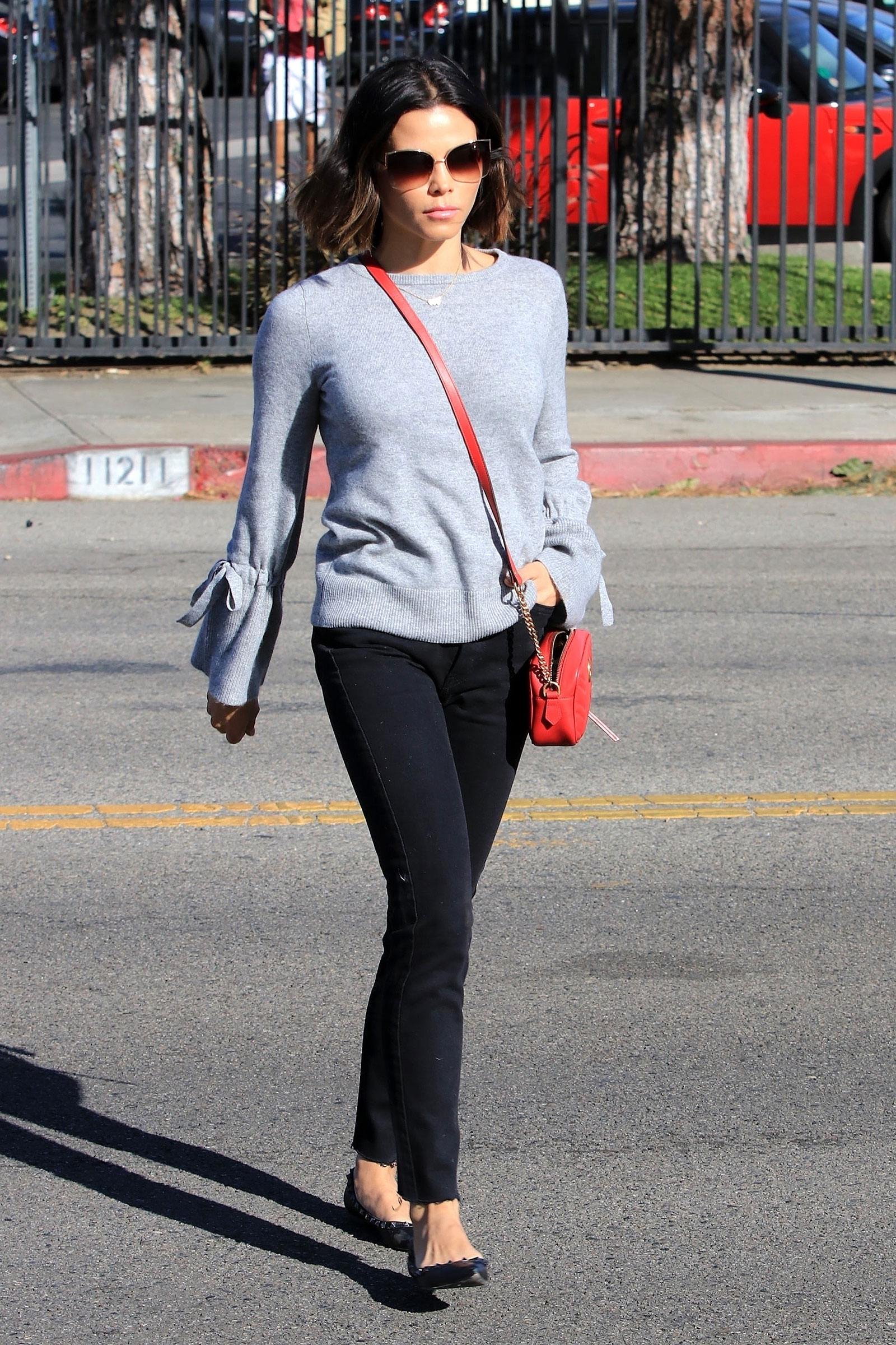 Jenna Dewan's tie-sleeve sweater, black pants and red bag look for less