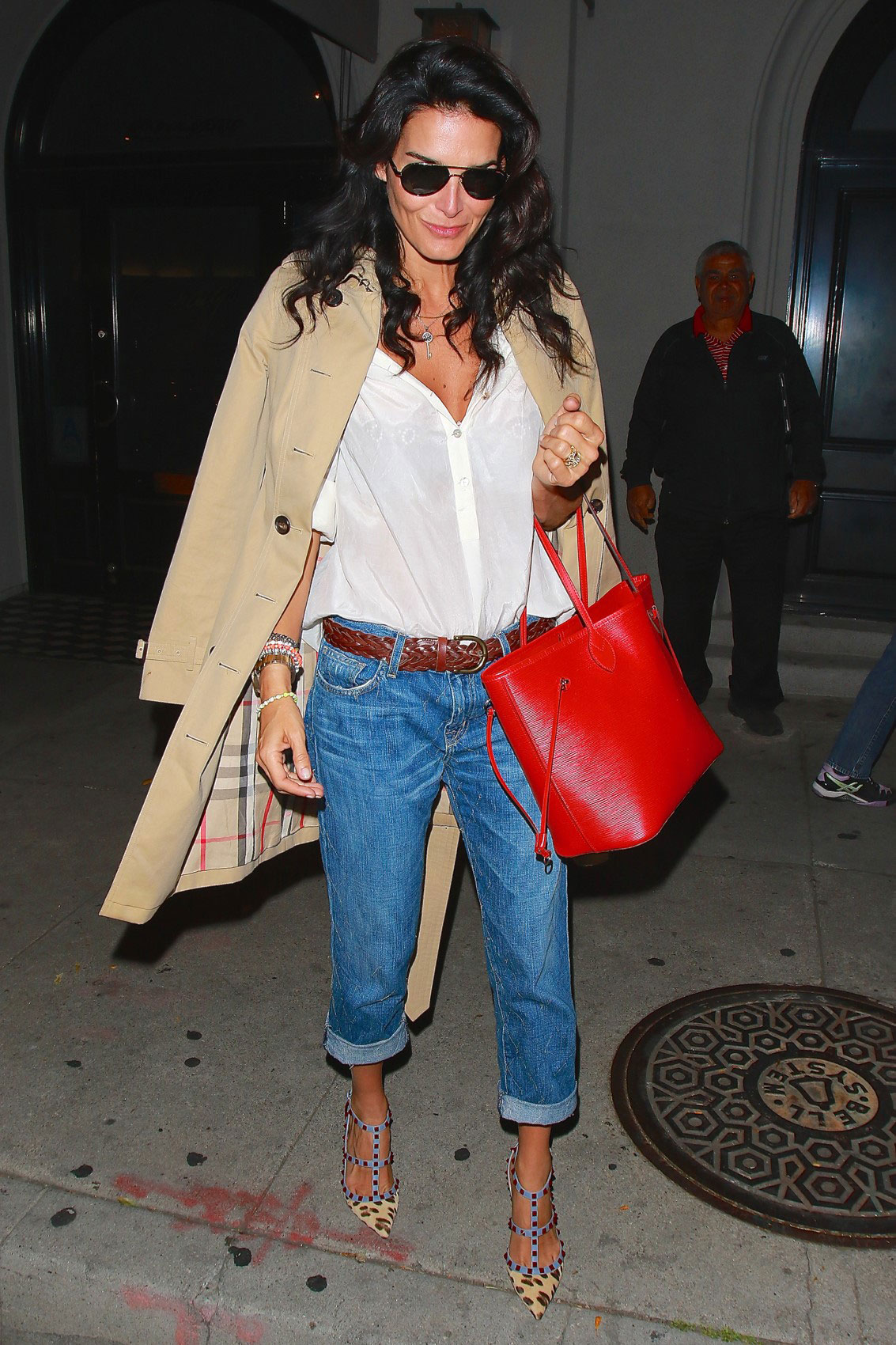 Actress Angie Harmon looks chic and sophisticated in a Burberry trench, white shirt, cuffed jeans and Rockstud heels.