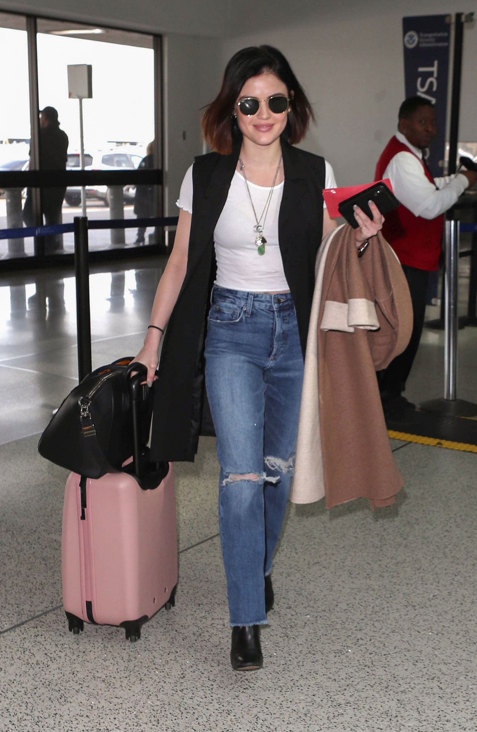 Lucy Hale wears a white tee, black longline vest and boyfriend jeans while traveling through LAX.