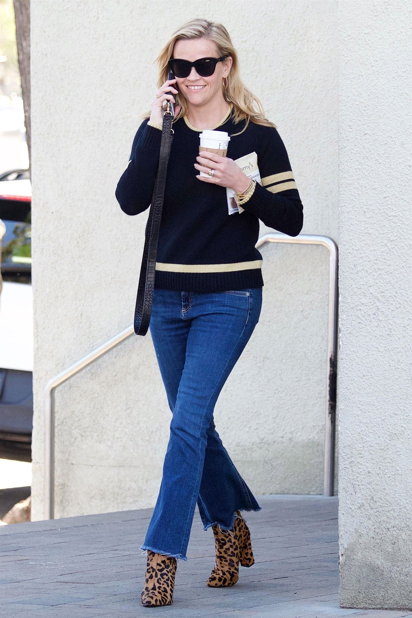 Reese Witherspoon wears her Draper James Spirit sweater with crop jeans and leopard print ankle booties.