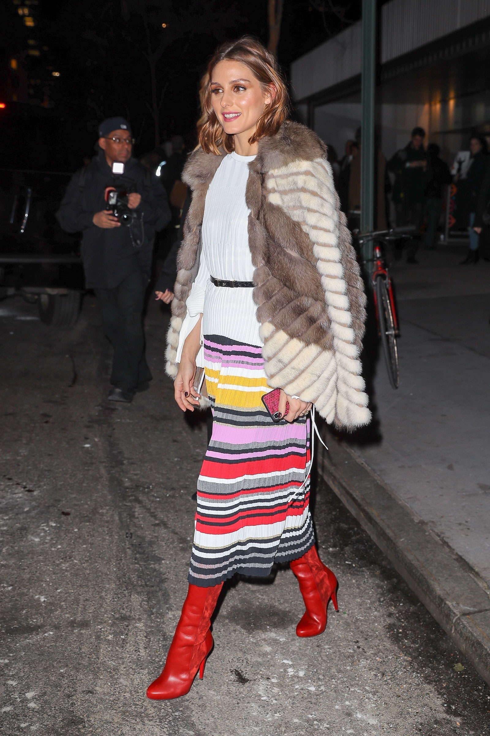 Olivia Palermo attends the Carolina Herrera show at NYFW in a striped midi skirt, tall red boots and fur cape.