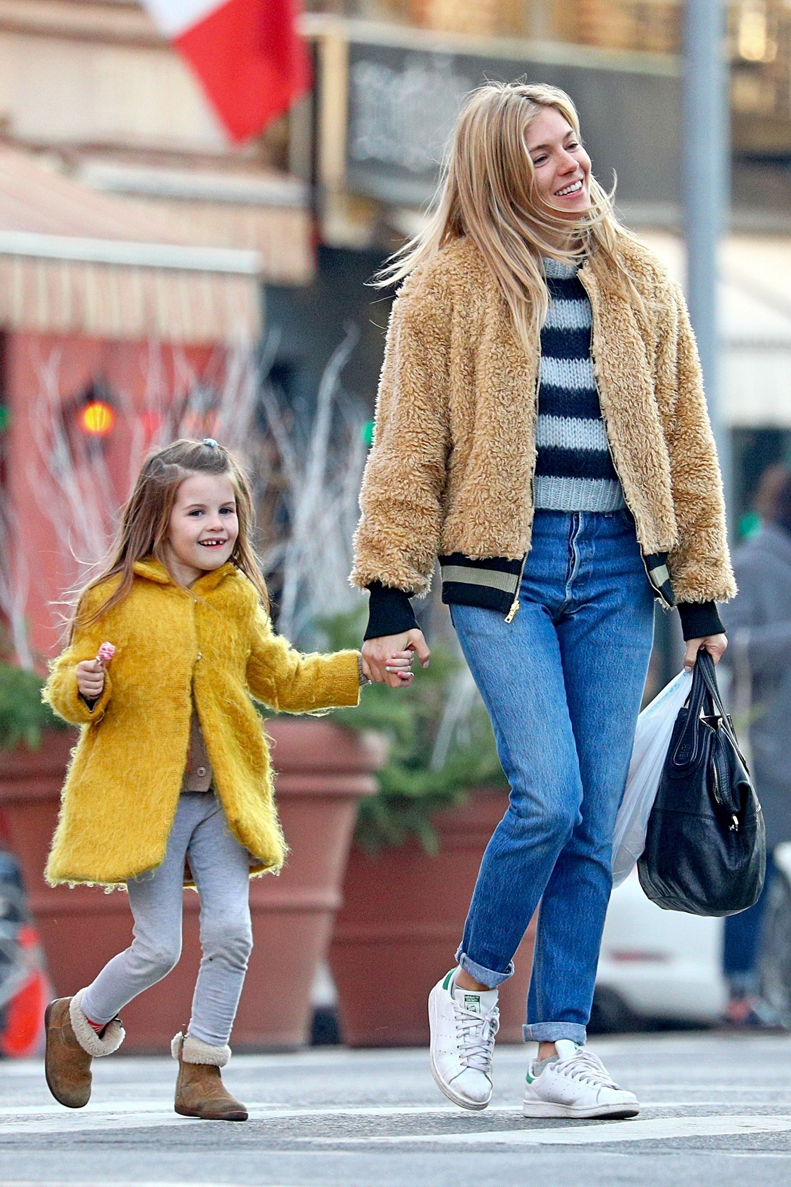Sienna Miller wears a faux fur bomber jacket with Adidas sneakers with daughter Marlowe while out and about in NYC.