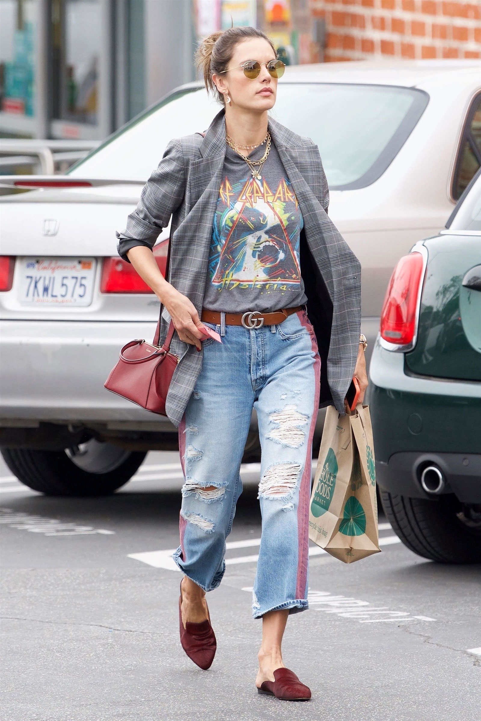 Alessandra Ambrosio's plaid blazer, band tee, Mother jeans, mules and Gucci belt look for less