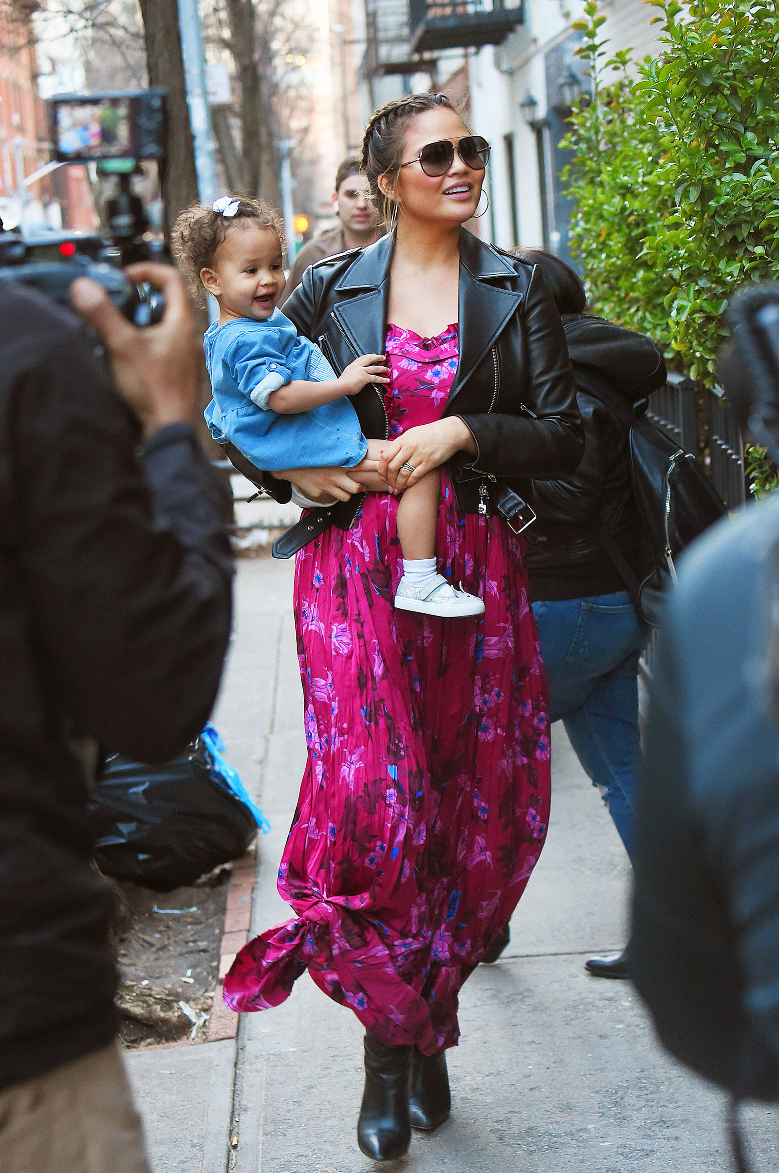 Chrissy Teigen's pregnancy style featuring floral maxi dress and black leather moto jacket