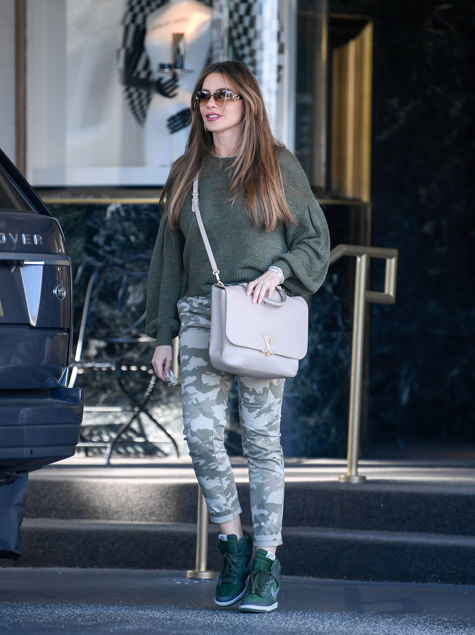 Sofia Vergara's dolman sleeve sweater, camo jeans and wedge sneakers look for less