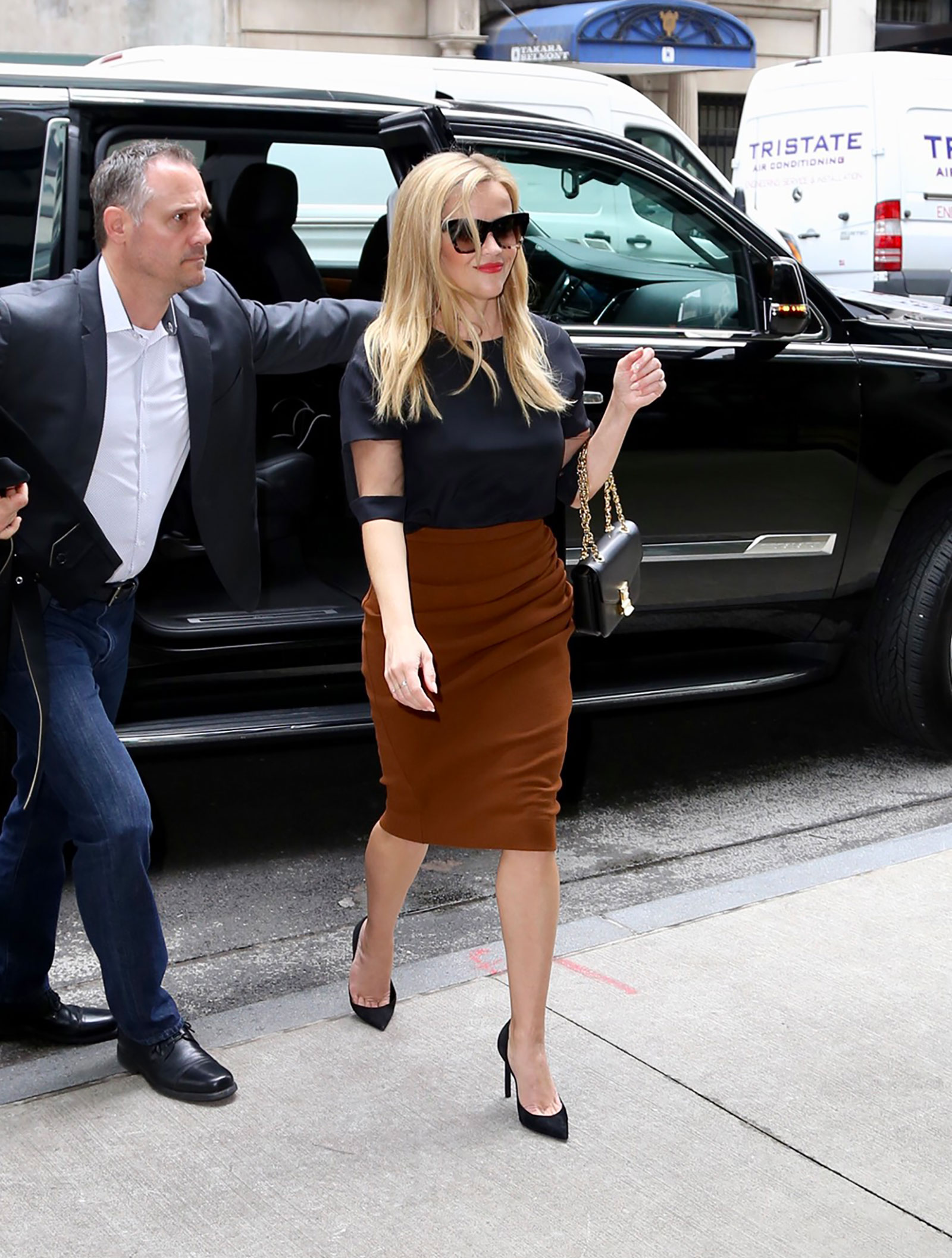 Reese Witherspoon's orange skirt and black top with mesh panels