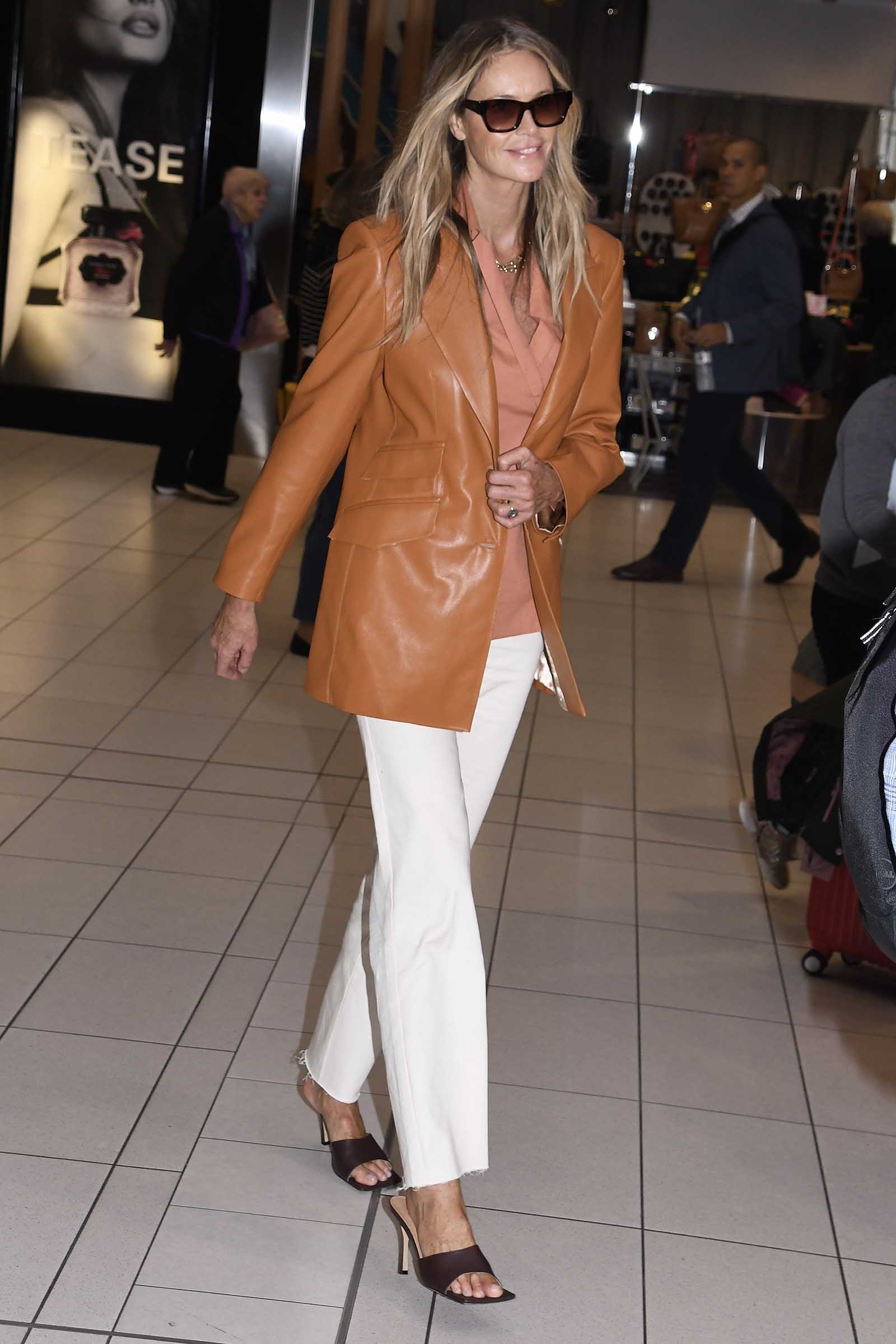 Elle Macpherson serves style in a brown leather jacket and wide leg pants!