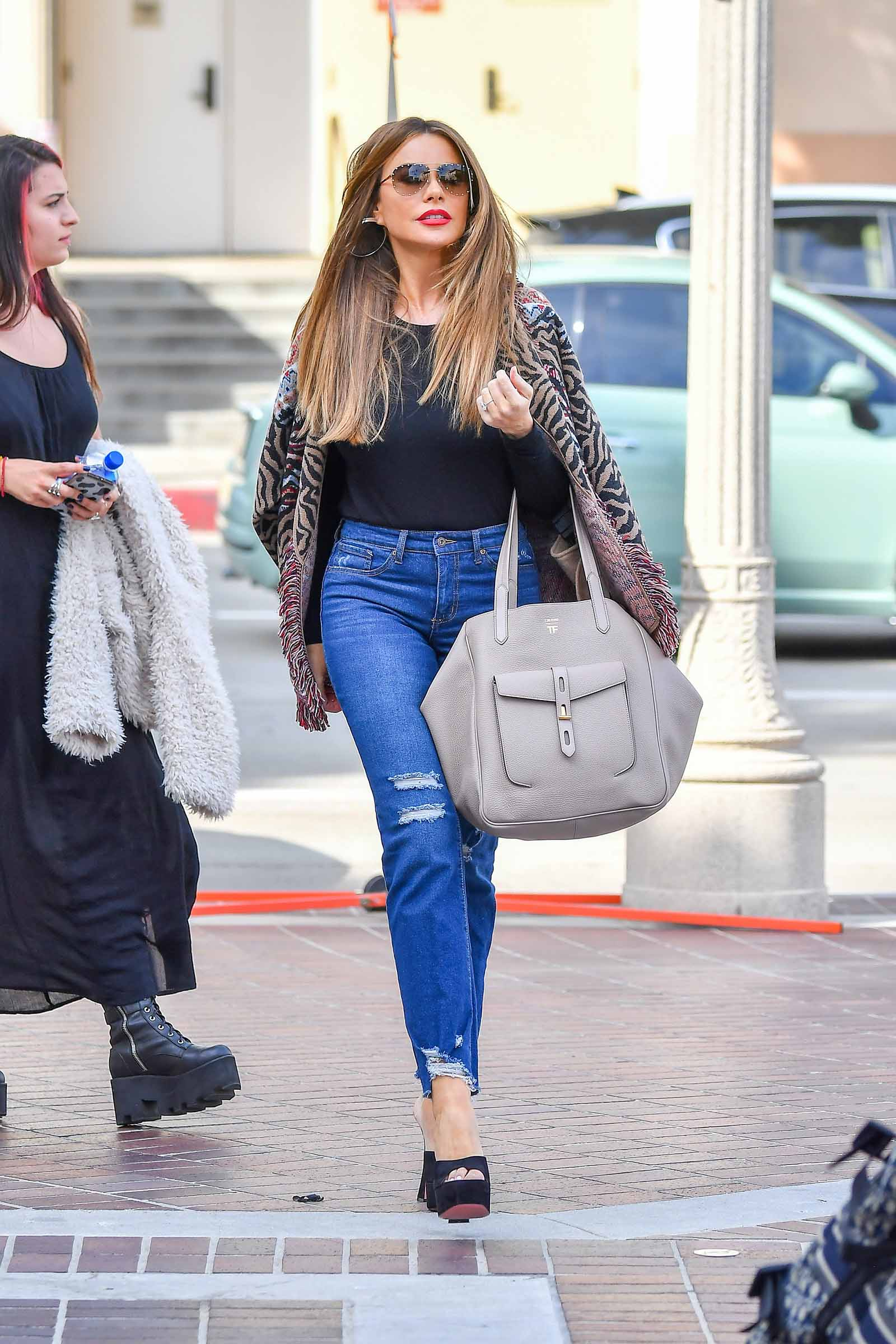 Sofia is chic in a cardigan and jeans.
