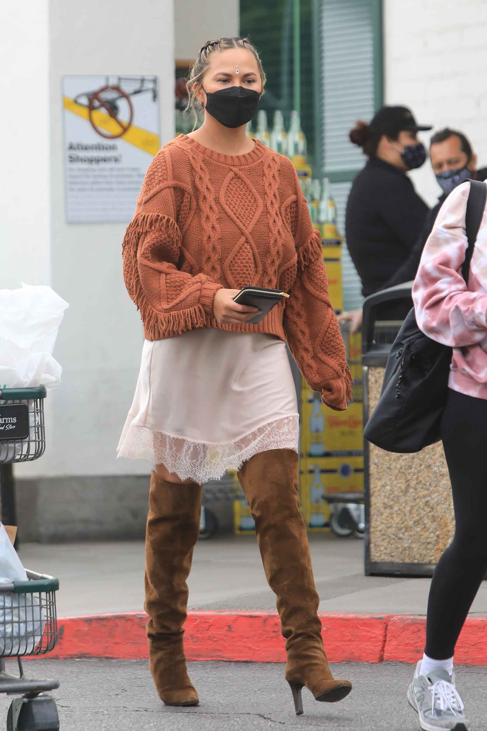 Chrissy Teigen's slip dress and over the knee boots look for less
